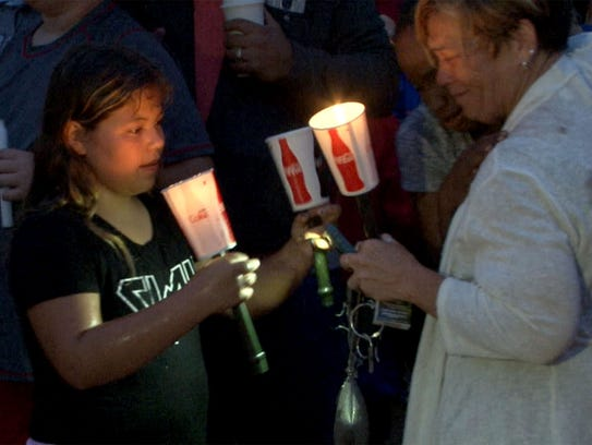 Brooklynn Rinck, 11, holds candles during a memorial