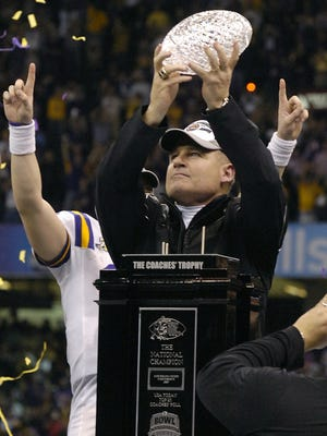 LSU head coach Les Miles holds up the Coaches Trophy after defeating the Ohio State Buckeyes in the BCS Championship game.