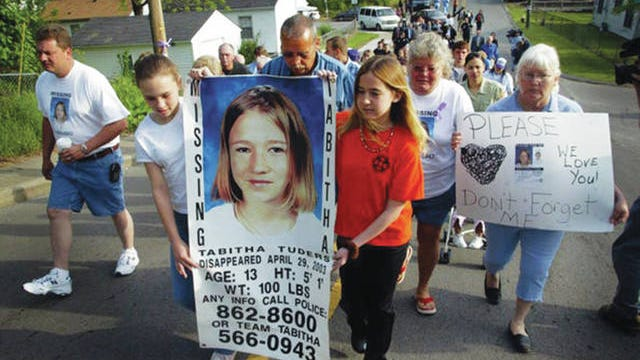 Family members and friends search for Tabitha Tuders as they walk to her bus stop on the anniversary of her disappearance in 2004.
