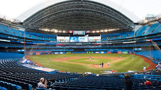 Photographers cover the game in an empty stadium during fourth-inning intrasquad baseball game action in Toronto on Friday.