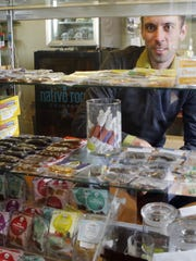 "Matt Brown, co-owner of Denver's ""My 420 Tours,"" looking over a sampling of marijuana edibles at a dispensary in Denver."