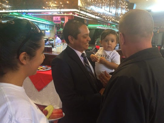 Oxnard City Council candidate Daniel Chavez talks to voters while holding his daughter, Pauline.