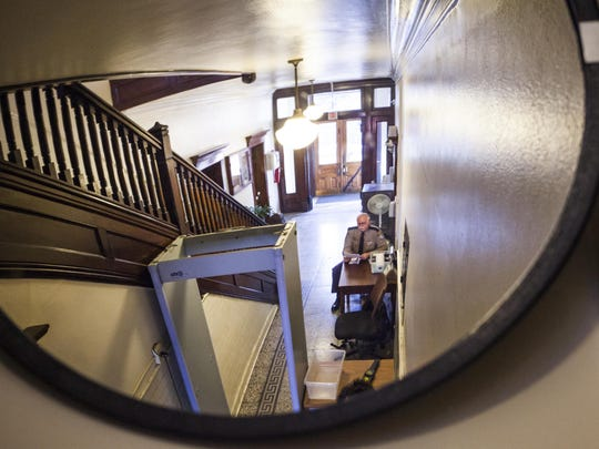 In this 2015 photo, Augusta County Sheriff's deputy J.M. Wieger is seen through a mirror that also shows both the exit and entrance at Augusta County Circuit Court.