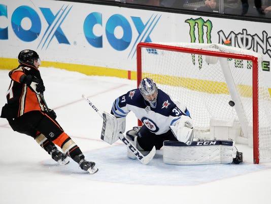 Anaheim Ducks' Adam Henrique, left, scores against Winnipeg Jets goaltender Connor Hellebuyck during the shootout in an NHL hockey game Thursday, Jan. 25, 2018, in Anaheim, Calif. The Ducks won 4-3. (AP Photo/Jae C. Hong)