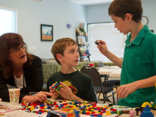 Kathryn Hunter, the executive director of NAMI of Collier County, looks on as Maxwell Wendt, 8, center and his brother, Matthew, 11, build with LEGOs at the NAMI office in Naples. Both brothers have been helped by the organization's HUGS program that helps families find mental health services.