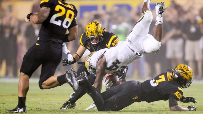 UCLA running back Paul Perkins is upended by ASU defensive back Damarious Randall (3) as ASU linebacker Viliami Moeakiola (28) and safety Jordan Simone look on during the second quarter of the college football game on Thursday, Sept. 25, 2014, at Sun Devil Stadium in Tempe, Ariz.