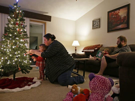 Megann Hooyman and her daughter, Callie, adjust the Christmas tree Tuesday while her husband, Andy, reads to  Rylee in the Appleton duplex they are renting while their house, damaged in an early December fire, is repaired.
