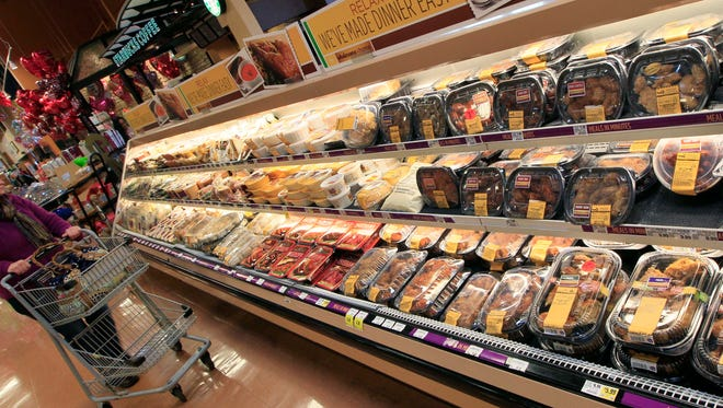 A customer checks out the ready-made food section at a grocery store in Cincinnati.