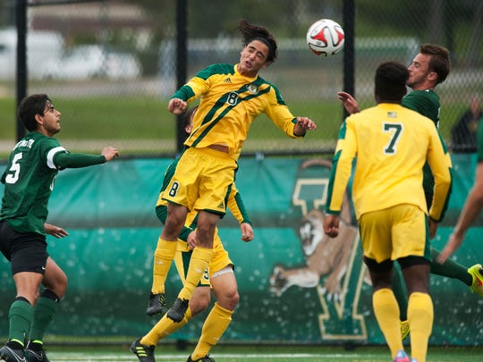 Vermont's Daniel Giron (8) heads the ball during the men's soccer game between the Dartmouth Big Green and the Vermont Catamounts at Virtue Field last season.
