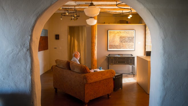 Donald Brenner sits in the Unsettled Gallery. Run by his wife Catherine Brenner, the gallery is housed in a building originally constructed around 1890 and added to over time.