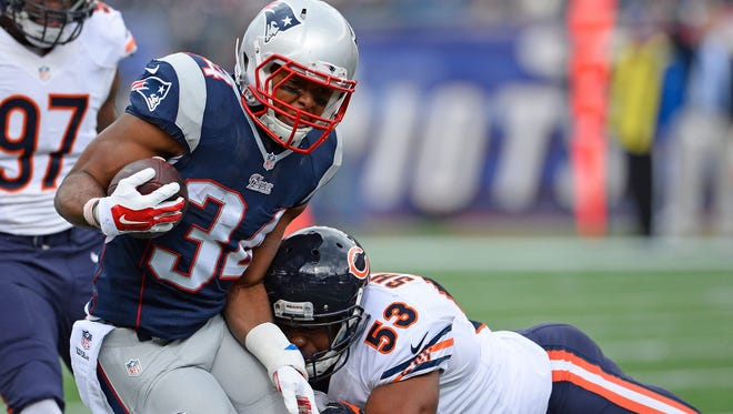 New England Patriots running back Shane Vereen, left, is tackled by Chicago Bears linebacker Darryl Sharpton on Sunday, Oct. 26, 2014.
