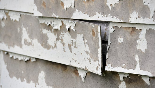 Paint and siding are shown peeling from an area home. Low- to moderate-income residents in St. Cloud can apply for rehabilitation loans through St. Cloud HRA.