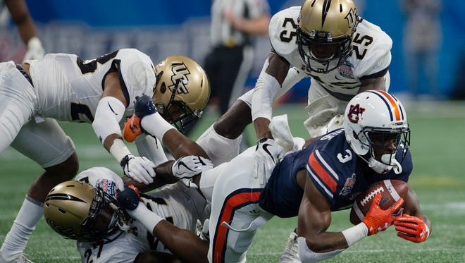UCF defensive back Richie Grant (27) tackles Auburn wide receiver Nate Craig-Myers (3) during the first half of the Peach Bowl between Auburn and Central Florida on Monday, Jan. 1, 2018, at Mercedes-Benz Stadium in Atlanta, Ga.
