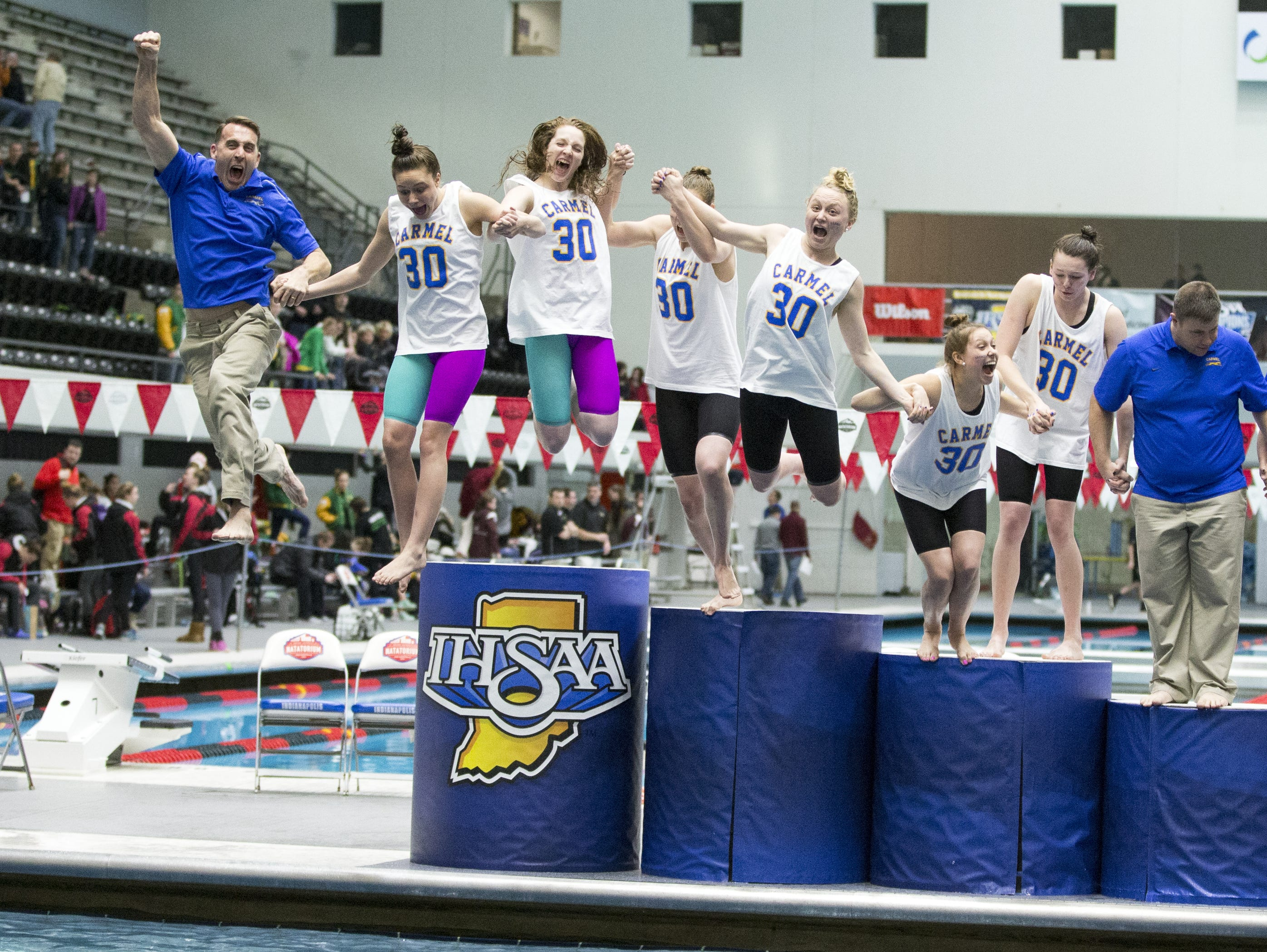 Carmel swimmers and coaches jump into the water after winning their 30th straight state title, a new national record in any sport.