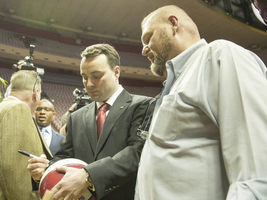 Todd Reid, Bloomington (right), gets the first signature from Archie Miller after he was introduced as the new men's basketball coach in Assembly Hall, Monday.