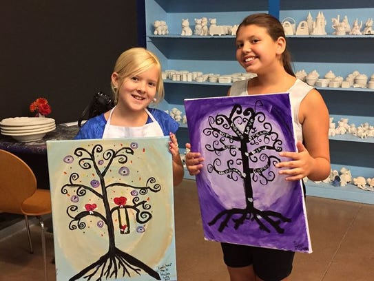 Two girls display their canvas paintings they made