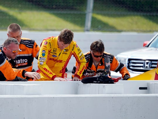 Ryan Hunter-Reay is helped from his car after wrecking