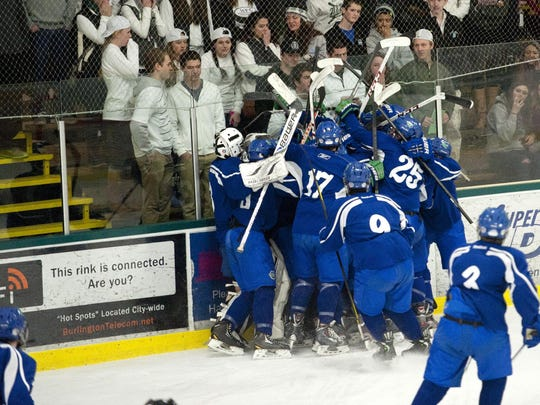 Colchester celebrates their 3-2 win over South Burlington with only 10 seconds remaining in sudden death overtime at Wednesday's boys high school hockey quarterfinal game at Leddy Arena.