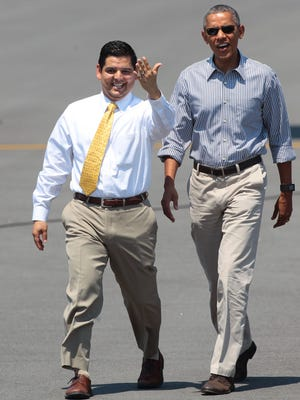 Congressman Raul Ruiz and U.S. President Barack Obama walk toward Ruiz's newborns during the president's fifth visit to the Coachella Valley on June 20, 2015.