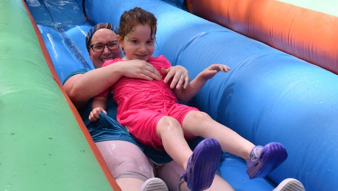Sara Murrell slides down a water slide with her daughter, Ivy Murrell, 5, at Water Play Day on Saturday at the Alexandria Zoo.