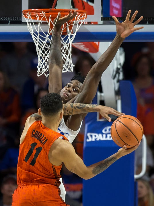 Florida guard Chris Chiozza (11) attempts a shot over Kentucky forward Jarred Vanderbilt (2) during the second half of an NCAA college basketball game in Gainesville, Fla., Saturday, March 3, 2018. Florida won 80-67. (AP Photo/Ron Irby)