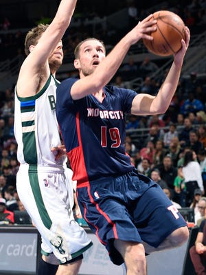 Pistons' Beno Udrih scores over the Bucks' Matthew Dellavedova in the second quarter.