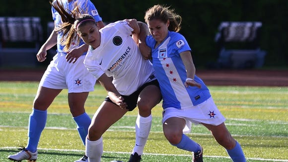 West Henderson alum Lydia Vandenbergh, right, battles U.S. national player Alex Morgan for a ball during a 2013 game.