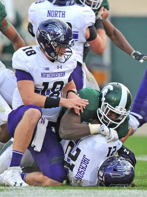 Wildcat quarterback Clayton Thorson (18) can't keep Spartan defender Malik McDowell from dropping his running back Justin Jackson (21) for a big loss.