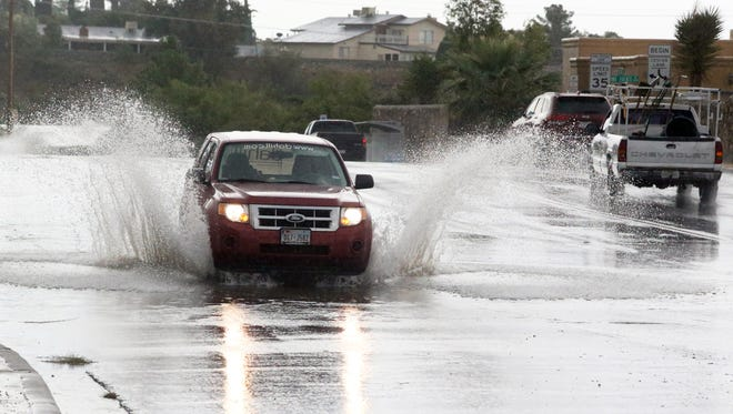 Drivers make their way along Westwind in a steady rainfall in West El Paso in 2016.