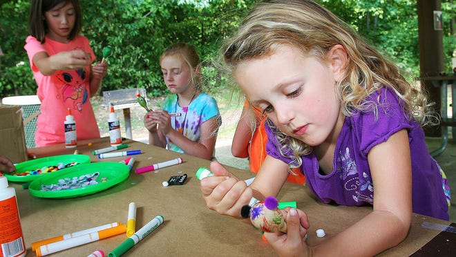 Olivia Jones adds color to her maraca at a creative station. Arts in the Park