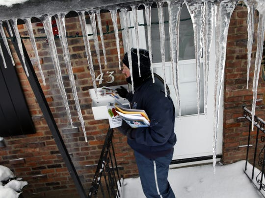 Letter carrier Jeff Gebhard of Greece works through the snow, cold and icicles as he delivers mail in Charlotte in 2010.