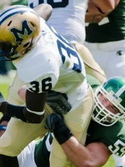 Adam Decker (bottom) of MSU wraps up Ricky Evans of Montana State during their game Saturday September 5, 2009 in East Lansing. KEVIN W. FOWLER PHOTO