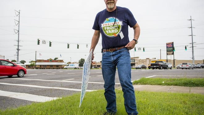 Bill Riehl, a Project Front Yard enforcer for the Lafayette Consolidated Government, removes an illegal sign from a public right-of-way at the corner of Ambassador Caffery Parkway and Johnston Street in Lafayette, La., Thursday, July 2, 2015.