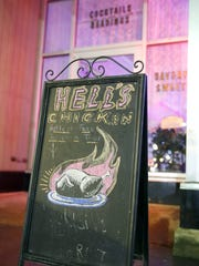 "A sign advertises The Spirit Room's spicy ""Hell's Chicken"" fried chicken."