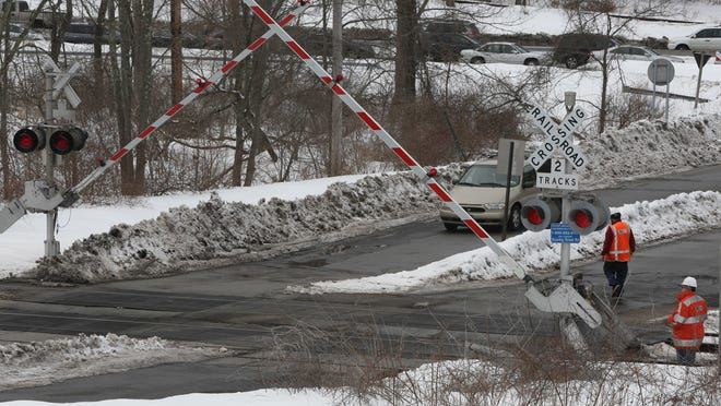 Metro-North Railroad employees test the crossing signals and safety arms at the Roaring Brook Road railroad crossing in Chappaqua on Saturday. Mount Kisco's Cynthia Parent backed through the gate seconds before a Metro-North train arrived.