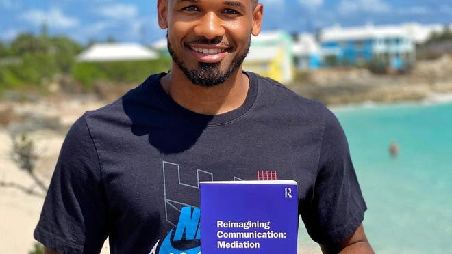 Former Hendersonville High multi-sport standout Grant Rivers poses with his book recently in Bermuda.