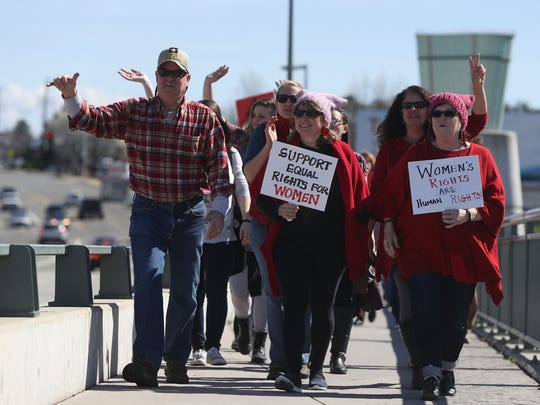 Around 100 people march along the Cypress Avenue Bridge on Wednesday during International Women's Day.