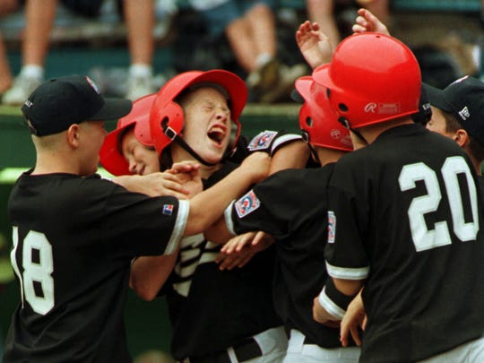 Team East's Todd Frazier from Toms River, N.J., center, gets mobbed by his teammates after hitting a two-run home run in the fourth inning against team South, from Greenville, N.C., at the Little League World Series in Williamsport, Pa., Tuesday, Aug. 25, 1998. The East came from behind to win 5-3.