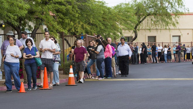 Voters wait in line to cast their ballots Tuesday at Red Mountain United Methodist Church in Mesa.