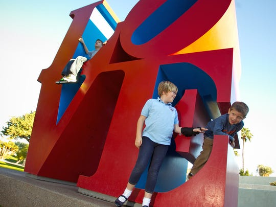 From left, Brody Meinz, 10, Violet Stanley, 7, and Henry Meinz, 5, all of Scottsdale, play on the LOVE sculpture at Scottsdale Civic Center Mall on Tuesday, November 22, 2011.