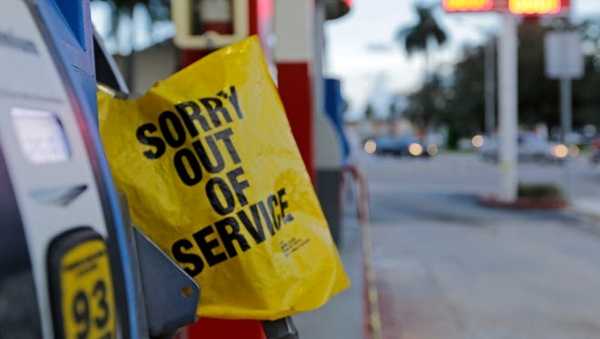 A gas pump is covered after a gas station ran out of gas, Thursday, Sept. 7, 2017, in Miami. South Florida officials are expanding evacuation orders as Hurricane Irma approaches, telling more than a half-million people to seek safety inland.