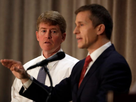 Democratic gubernatorial candidate Chris Koster, left, listens to Republican challenger Eric Greitens during the first general election debate in the race for Missouri governor at  the Missouri Press Association convention Friday, Sept. 30, 2016, in Branson, Mo.