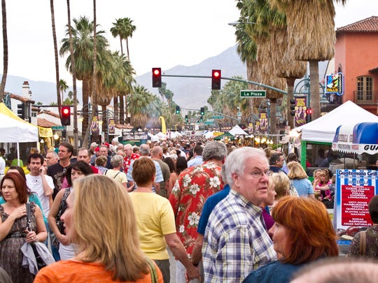People browse art, craft and food booths at VillageFest,