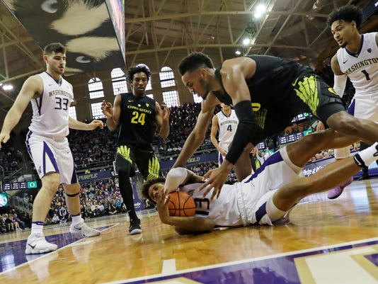 Oregon forward Troy Brown, center right, reaches for a loose ball held on the ground by Washington forward Hameir Wright in the second half of an NCAA college basketball game, Saturday, March 3, 2018, in Seattle. Oregon won 72-64. (AP Photo/Ted S. Warren)
