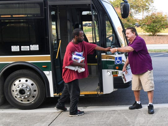 In this file photo, Darius Cowan, left, of Anderson gives bus driver Jerry Jenkins a ticket before getting on an Electric City Transit bus. Anderson learned Tuesday that it will receive about $74,000 in VW Dieselgate settlement funds to help pay for a bus that runs on clean-burning natural gas.