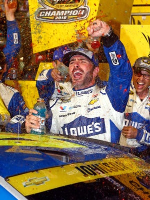 Jimmie Johnson celebrates winning the Ford Ecoboost 400 and his record-tying seventh NASCAR Sprint Cup championship.