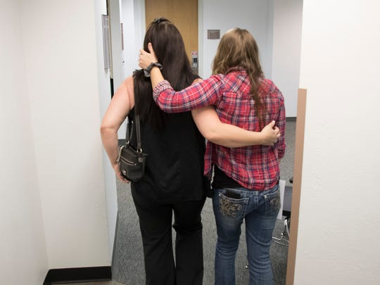 Deanna Birrell and Destiny Swan embrace after leaving a courtroom at the Lee County Courthouse on Monday. The two were leaving a custody hearing involving Swan's daughter, Ava. Birrell was raising Ava. A magistrate issued custody to Matthew Bolton after a DNA test proved he was the father.