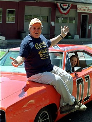 """FILE - In this Aug. 10, 1999, file photo, """"Cooter,"""" actor Ben Jones, sits atop one of the 229 hotrods, named the General Lee, used in the show """"Dukes of Hazzard"""" as ecstatic fan, Aliceson Johnson, of Charlottesville, Va., sits in the drivers seat in front of his store in Sperryville, Va. In a Facebook posting to fans of the show on Tuesday, June 23, 2015, Jones defended the Confederate flag as a symbol of the spirit of independence. (AP Photo/Steve Helber, File)"""