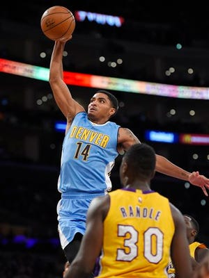 Denver Nuggets guard Gary Harris goes up for a dunk as Los Angeles Lakers forward Julius Randle watches during the first half of an NBA basketball game, Tuesday, Nov. 3, 2015, in Los Angeles. (AP Photo/Mark J. Terrill)