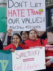 "Protesters hold signs as they yell at a rally outside of City Hall in San Francisco, Wednesday, Jan. 25, 2017. President Donald Trump moved aggressively to tighten the nation's immigration controls Wednesday, signing executive actions to jumpstart construction of his promised U.S.-Mexico border wall and cut federal grants for immigrant-protecting ""sanctuary cities."""